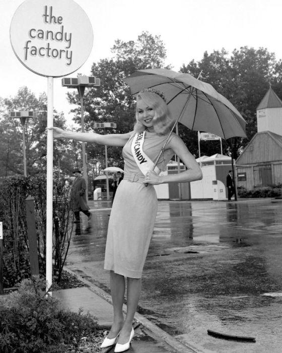 Актриса Джо Лэнсинг позирует с зонтиком за пределами павильона «Chunky Candy» на Всемирной выставке.